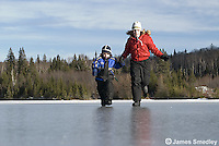 Boy and girl running and sliding on the frozen lake ice