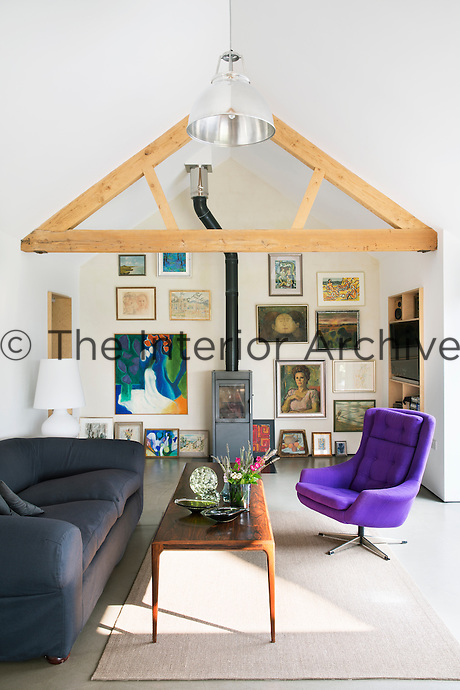 The living room features a wood-burning stove from Heta and a wall of artworks, including a large painting by the late artist Peter Campbell. The table is a vintage Norwegian piece and the 1960s chair has been re-covered in a bold purple upholstery.
