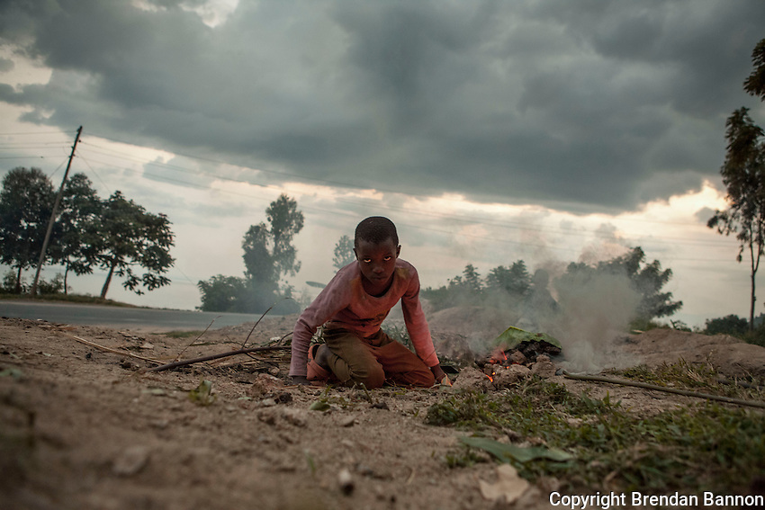 While thier goats are grazing in a rock quarry a group of children cook potatoes to eat at dusk along  Lake Kivu in Gisenyi, Rwanda.  Photo By Brendan Bannon March 5, 2014