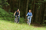 Couple riding bikes in wooded area