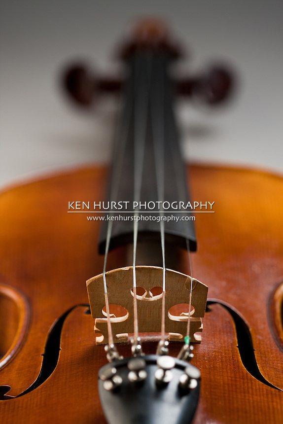 Narrow depth of field view focused on the bridge and strings of a classical violin or fiddle.