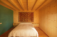 The sparely furnished guest bedroom features a green painted wall and a colourful tapestry