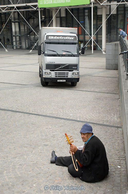 An elderly Romanian gypsy busking outside the Pompidou Centre in central Paris.