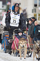 Christian Turner and team leave the ceremonial start line with an Iditarider at 4th Avenue and D street in downtown Anchorage, Alaska during the 2015 Iditarod race. Photo by Jim Kohl/IditarodPhotos.com