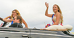 Wantagh, New York, USA. 4th July 2015. A finalist contestant in The Miss Wantagh Pageant ceremony, a long-time Independence Day tradition on Long Island, waves as she rides in backseat of a luxury convertible car, with woman in front seat about to throw out candy to viewers, in the town's July 4th Parade. After the parade, the Miss Wantagh Pageant 2015 ceremony was held. Since 1956, the Miss Wantagh Pageant, which is not a beauty pageant, crowns a high school student based mainly on academic excellence and community service.