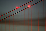 The Golden Gate Bridge cables outline a whisp of fog during the evening twilight in San Francisco, California.