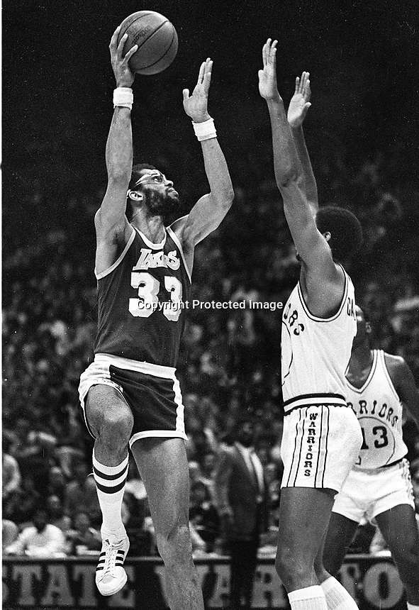 Los Angles Laker Kareem Abdul Jabbar shooting over Golden State Warrior Joe Barry Carroll. (1981 photo/Ron Rfiesterer)