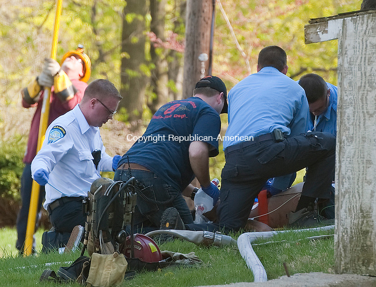 WATERBURY, CT 27 APRIL 2013--042713JS03--Emergency personnel tend to a person that was pulled from a burning home on Tremont Street in the Bunker Hill section of Waterbury on Saturday. . Jim Shannon Republican-American.