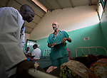 "Dr. Tom Catena, a Catholic lay missionary from the United States, treats a patient in the Mother of Mercy Hospital in Gidel, a village in the Nuba Mountains of Sudan. The area is controlled by the Sudan People's Liberation Movement-North, and frequently attacked by the military of Sudan. The Catholic hospital, at which Catena is often the only physician, is the only referral hospital in the war-torn area. Catena is popularly referred to as ""Doctor Tom""."