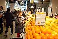 Shopper chooses oranges in the new Whole Foods Market opposite Bryant Park in New York on opening day Saturday, January 28, 2017. The store in Midtown Manhattan is the chain's 11th store to open in the city. The store has a large selection of prepared foods from a diverse group of vendors inside the store.  (© Richard B. Levine)
