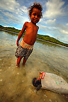 Child posing a the front of the camera with a bag of sea cucumbers in the village of Hessessai Bay at PanaTinai (Panatinane)island in the Louisiade Archipelago in Milne Bay Province, Papua New Guinea.  The island has an area of 78 km2..The Louisiade Archipelago is a string of ten larger volcanic islands frequently fringed by coral reefs, and 90 smaller coral islands located 200 km southeast of New Guinea, stretching over more than 160 km and spread over an ocean area of 26,000 km? between the Solomon Sea to the north and the Coral Sea to the south. The aggregate land area of the islands is about 1,790 km? (690 square miles), with Vanatinai (formerly Sudest or Tagula as named by European claimants on Western maps) being the largest..Sideia Island and Basilaki Island lie closest to New Guinea, while Misima, Vanatinai, and Rossel islands lie further east..The archipelago is divided into the Local Level Government (LLG) areas Louisiade Rural (western part, with Misima), and Yaleyamba (western part, with Rossell and Tagula islands. The LLG areas are part of Samarai-Murua District district of Milne Bay. The seat of the Louisiade Rural LLG is Bwagaoia on Misima Island, the population center of the archipelago.PanaTinai (Panatinane) is an island in the Louisiade Archipelago in Milne Bay Province, Papua New Guinea. The island has an area of 78 km2..The Louisiade Archipelago is a string of ten larger volcanic islands frequently fringed by coral reefs, and 90 smaller coral islands located 200 km southeast of New Guinea, stretching over more than 160 km and spread over an ocean area of 26,000 km? between the Solomon Sea to the north and the Coral Sea to the south. The aggregate land area of the islands is about 1,790 km? (690 square miles), with Vanatinai (formerly Sudest or Tagula as named by European claimants on Western maps) being the largest..Sideia Island and Basilaki Island lie closest to New Guinea, while Misima, Vanatinai, and Rossel islands lie further east..The archi