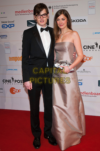 SAM RILEY & ALEXANDRA MARIA LARA .The 24th European Film Awards 2011 at Tempodrom, Berlin, Germany. .December 3rd, 2011.full length black tuxedo white shirt bow tie glasses strapless beige dress couple clutch bag silver .CAP/PPG/NK.©Norbert Kesten/People Picture/Capital Pictures