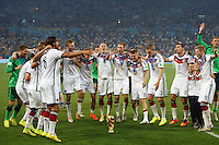 The Germany team dance around the World Cup trophy