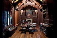 The banqueting hall is a gothic extravaganza, clad in dark wood panelling, with medieval furniture and heraldry