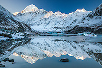 Mirror reflections of Aoraki Mt Cook, the Cook Range and the Southern Alps in Hooker Glacier Terminal Lake. Rock in foreground.  Aoraki Mt Cook National Park, South Canterbury New Zealand.
