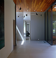 Steel and glass combine with a cedar wood ceiling in this contemporary entrance hall