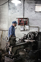 A machinist working at a small shop in Xingxing village on the outskirts of Shanghai,  China on 14 August 2015.  As China's sputtering economy has beginning to affect employment, many migrants who used to live in the village to work on Shanghai's numerous construction sites and factories are beginning to thin out.