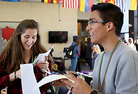 NWA Democrat-Gazette/DAVID GOTTSCHALK Elizabeth Ellington (left), a sophomore at the University of Arkansas, and Cesar Quiodetti, a freshman, cut out jester style hats Monday, February 12, 2018, during the Beads and Bling It's a Mardi Gras Thing in the Arkansas Union International Connections Lounge on the campus in Fayetteville. The celebration, hosted by University Programs, offered King Cake, mask decorating, trivia and other activities.