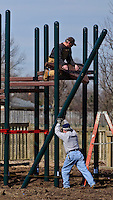 City workers attach platforms to newly installed metal posts at Planet Westerville as the original wooden playground is replaced with a metal structure that promises to be more durable and safe. The only remaining piece of the original structure is the entrance with its wooden towers. Photo Copyright Gary Gardiner. Not be used without written permission detailing exact usage.