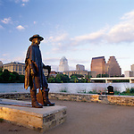 a seated woman enjoys the view of downtown Austin with Stevie Ray Vaughn Memorial Statue along with views of the skyline and town lake.