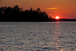 Sunset over the waters of Lake Kabetogama in Voyager National Park. The Park is in the Border Lakes region of northern Minnesota and northwestern Ontario. This forested, lake-filled landscape covers 5.1 million acres surrounding Quetico Provincial Park, Voyageurs National Park and the Boundary Waters Canoe Area Wilderness. This region is part of the Superior National Forest in northeastern Minnesota.