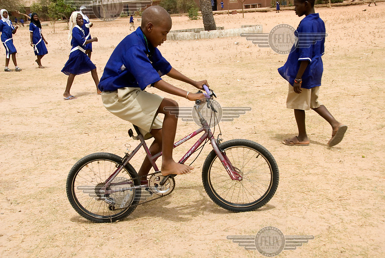 Alieu Jallow, who is blind, rides his bicycle through the playground of Bakoteh lower basic school....