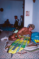 Jamie Brisick (USA) preparing his surfboard on French island of Reunion in the Indian Ocean. Brisick was there for a Quiksilver surf trip. Circa 1989 Photo: joliphotos.com
