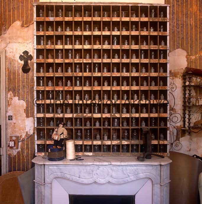 A collection of small glass bottles are arranged neatly in a wooden frame above a marble fireplace. The torn wallpaper on either side gives the room a neglected air.