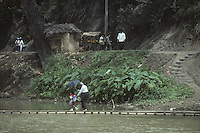 A man helps a young boy cross a river in Sri Lanka in 1996.
