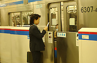 People commute on Tokyo's busy underground system. The steel doors are designed to stop people committing suicide by throwing themselves in front of trains.