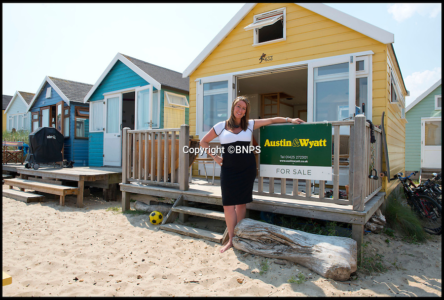 BNPS.co.uk (01202 558833)<br /> Pic: LauraDale/BNPS<br /> <br /> Sales Manager Victoria Berry from Austin & Wyatt stands outside the property.<br /> <br /> A modest beach hut with no bathroom or mains electricity has gone on the market for a whopping 270,000 pounds - making it the most expensive in Britain.<br /> <br /> The asking price for the tiny wooden shack on Mudeford Spit near Christchurch, Dorset, is the same cost as a plush three-bedroom house in some parts of the country and is as much as a top-of-the-range Ferrari car.<br /> <br /> The 18ft by 12ft hut can sleep up to 12 people - four people on a mezzanine deck, four on two sofa beds and another two on a pull-out bed.<br /> <br /> The huge asking price is because it is just a stones throw away from the water boasting stunning sea views out towards the Isle of Wight and the Needles.<br /> <br /> The current owners are selling the beach hut so that they can move to another one on the same sandy strip with a different view.