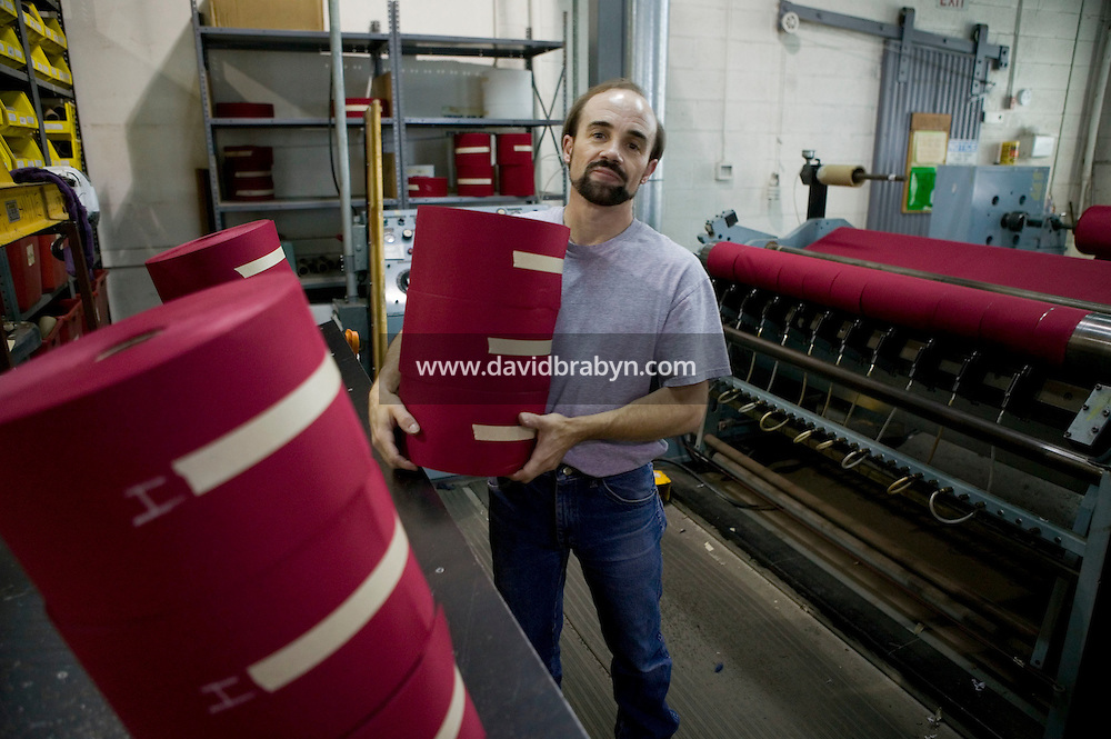 21 June 2005 - Oaks, PA - A worker carries freshly made rolls of polyester fabric that will be turned into red stripes at the Annin & Co. American flag manufacturing plant in Oaks, PA, USA. Photo Credit: David Brabyn.