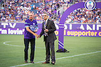 Orlando, Florida - Saturday, April 23, 2016: Orlando Pride President and Founder, Phil Rawlins, accepts an award from NWSL Commissioner Jeff Plush during the pre-game ceremony of an NWSL match between Orlando Pride and Houston Dash at the Orlando Citrus Bowl.