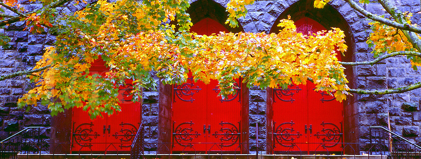 Arched red doors with elaborate ironowork hinges contrasts with stone walls and yellow fall foliage. autumn leaves, external architectural details.