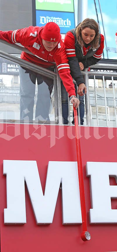 OSU students Jake Johnson and Leigh Hedrick work together to cover the M with red duct tape before the start of the rivalry game against Michigan at Ohio Stadium on November 29, 2014. (Chris Russell/Dispatch Photo)