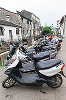 Suzhou, Jiangsu, China.  Motorbikes and Old Houses Line Sides of Shantang Canal, a Popular Tourist Destination.