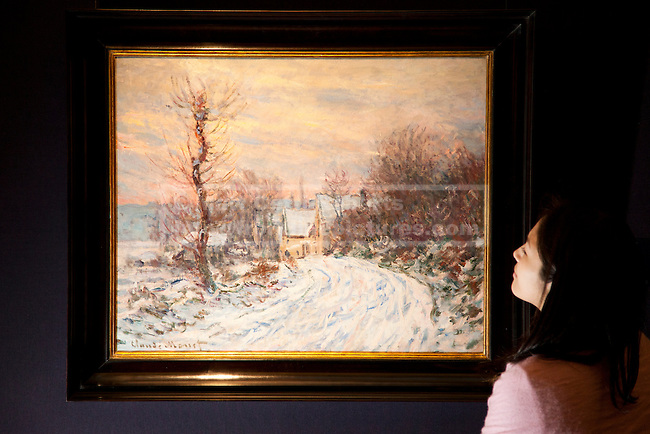01/02/2012. LONDON, UK. A member of Sotherby's looks at Claude Monet's 'L'entree de Giverny en hiver' ahead of an auction of Impressionist and Modern Art held on the 8th of February 2012. The previously unseen piece is estimated to raise £4,500,000-6,500,000. Photo credit: Matt Cetti-Roberts