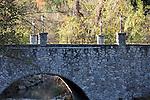 A stone arched bridge over a quaint quite creek