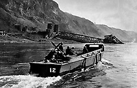 BNPS.co.uk (01202 558833)<br /> NARA/BNPS<br /> <br /> A USN Jeep-carrying LCVP motors past the fallen Ludendorff Railroad Bridge at Remagen on its Rhine River patrol.<br /> <br /> Remarkable rarely seen photos of heroic Allied soldiers fighting their way across Europe before crossing the River Rhine 75 years ago feature in a new book.<br /> <br /> They are published in Images of War, Montgomery's Rhine Crossing, which tells the story of the legendary offensive, nicknamed Operation Plunder, in March 1945.<br /> <br /> On the night of March 23, Field Marshal Bernard Montgomery's 21st Army Group launched a massive artillery, amphibious and airborne assault to breach the historic defensive water barrier protecting northern Germany.<br /> <br /> At the same time, the Americans, with the support of the British 6th Airborne Division, set in motion Operation Varsity - involving 16,000 paratroopers - on the east bank of the Rhine. They were dropped here to seize bridges to prevent German reinforcements from contesting the bridgeheads.<br /> <br /> Fierce fighting ensued, with much bloodshed on both sides as the Allies met determined resistance from machine gun nests. But the daring operation proved successful, helping to considerably shorten the war - the Nazis surrendered just six weeks later.