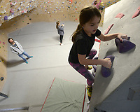 NWA Democrat-Gazette/ANDY SHUPE<br /> Vivian Higgins, 8, of Bentonville smiles Friday, Jan. 4, 2018, as she reaches the top of a climbing wall during a three-day Winter Climbing Camp at Ozark Climbing Gym in Springdale. Campers learned about climbing equipment, holds, routes and proper climbing and safety techniques.