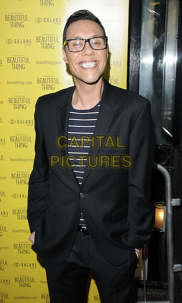 """Gok Wan.The """"Beautiful Thing"""" press night, The Arts Theatre, London, England..April 17th, 2013.half length black suit blue stripe top glasses hands in pockets smiling gold tooth.CAP/CAN.©Can Nguyen/Capital Pictures."""