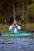 A woman watches wildlife through binoculars from a kayak at Blue Cypress Lake in Florid