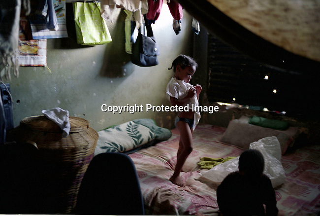 girl,bedroom,shelter,poverty,squatter,.A young girl gets dressed in the one-roomed shelter in a building being occupied in downtown Johannesburg, South Africa..©Per-Anders Pettersson/iAfrika photos
