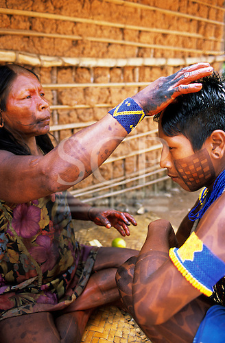 Bacaja village, Amazon, Brazil. A mother paints her son with Urucum for the hornets' nest initiation ceremony; Xicrin tribe.