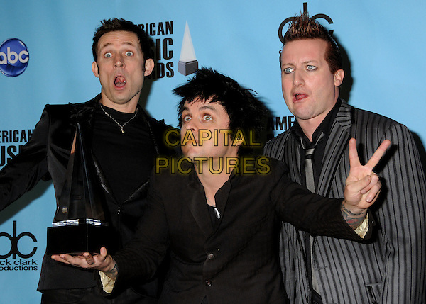 GREEN DAY - Mike Dirnt, Billie Joe Armstrong and Tre Cool.At the 2009 American Music Awards - Press Room held at the Nokia Theatre L.A. Live, Los Angeles, California, USA, .22nd November 2009..AMA AMAs half length grey gray jacket band group black suit suits pinstripe award trophy hand v peace sign gesture mouth open funny .CAP/ADM/BP.©Byron Purvis/AdMedia/Capital Pictures.