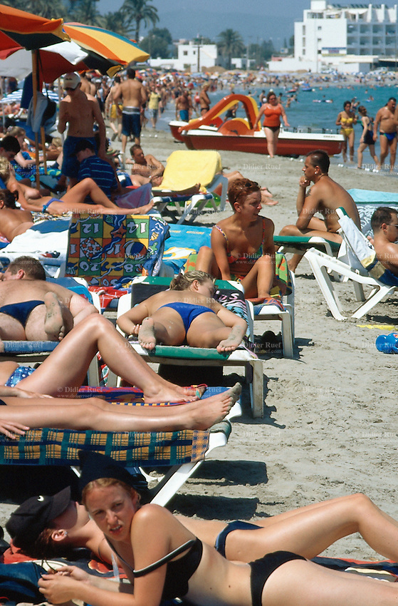 "Spain. Ibiza in the Balearic islands. Ibiza. Mediterranean sea. Beach "" Den Bossa"". Tourists take a rest and sunbathe aon the sandy beach. © 1999 Didier Ruef"