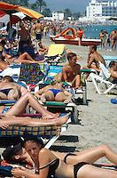 "Spain. Ibiza in the Balearic islands. Ibiza. Mediterranean sea. Beach "" Den Bossa"". Tourists take a rest and sunbathe aon the sandy beach. © 1999 Didier Ruef"