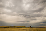 Abandoned red school house in harvested grain field, approaching storm. Louse Creek, Montana