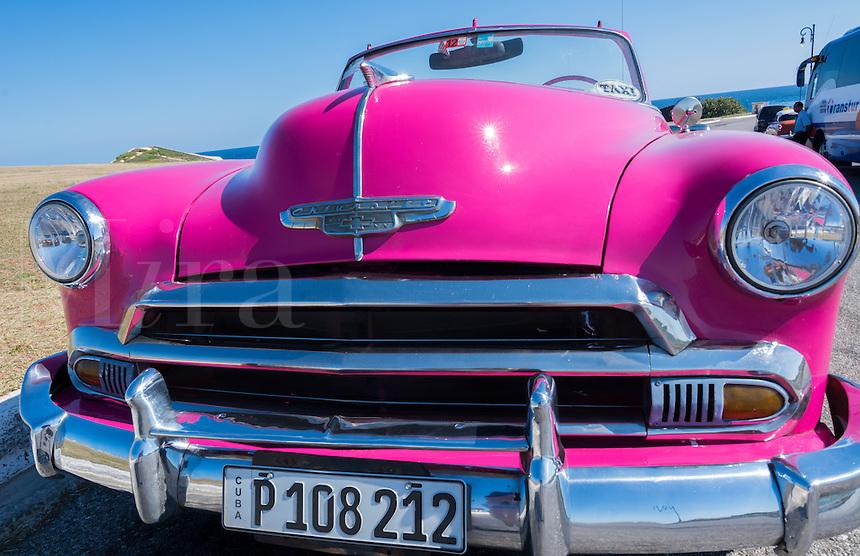 Havana Cuba pink classic 1950s auto in beautiful neighborhood of Habana parked
