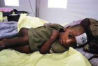 A sick Rwandan child lies listlessly in a cot in aan inpatient tent at the AmeriCares clinic in Buranga Rwanda, Oct., 1994. The New Canaan, Conn.  humanitarian organization set up the clinic halfway between the refugee camps in Goma, Zaire (now Congo) and the Rwandan capitol, Kigali.  The organization operated the clinic  from Aug., to Dec., 1994.They treated refugees on their way home as well as people living in the area suffering from ailments resulting from unclean living conditions as well as conflicts with neighbors and occasional discovery of unused ordinance littering the countryside.  The living conditions resulted from the destruction of the country's infrastructures in the genocide and civil war in 1994.